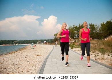 two women running on the beach - early morning summer workout