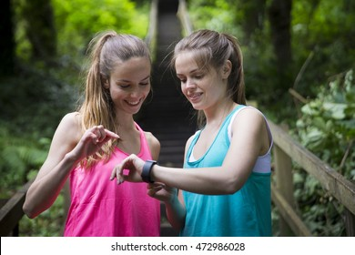 Two Women running on forest trail looking at a smart watch. Fitness healthy lifestyle concept with female athlete.