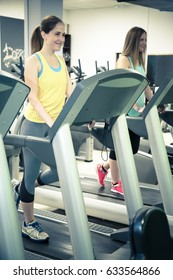 Two women running on treadmills in a gym. Fit girls exercising in gym and warming up on running tracks.
