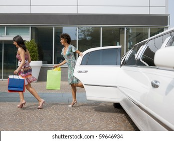 two women running out of limousine with shopping bags. Horizontal shape, full length