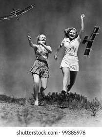 Two women running and playing with model airplanes