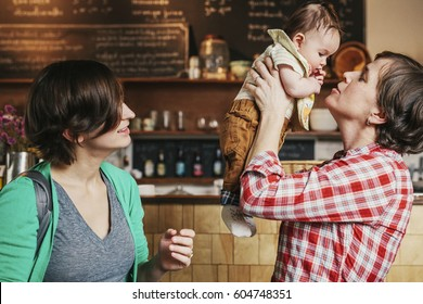 Two women, a same sex couple with their 6 month old baby in their coffee shop business owners and parents