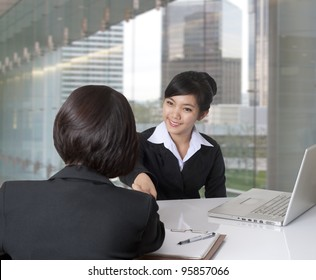 Two women shaking hands in the office