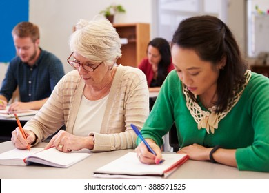 Two women sharing a desk at an adult education class