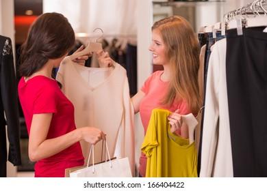 Two Women shopping choosing dresses. Beautiful young shoppers in clothing store.