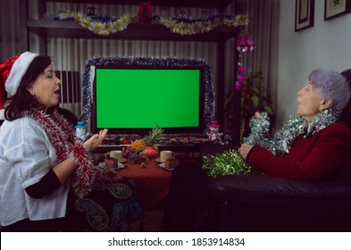 Two women singing Christmas carols while sitting in front of a green screen TV. The one on the left in a Santa hat or a caregiver or volunteer or caring daughter. Or maybe an actress of rental agency