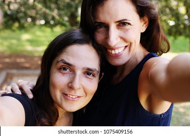 Two women sisters smiling with a green background
