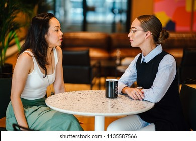 Two women sit down for a meeting in an office over a hot beverage (coffee or tea). One is an Asian Chinese woman and the other a Caucasian white woman. They are well dressed and having a discussion.