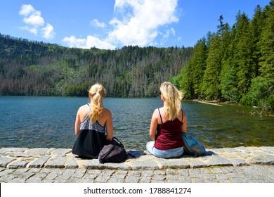 Two women sitting by Black lake (Cerne jezero) in the National park Sumava, Czech Republic. - Shutterstock ID 1788841274