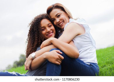 Two women sitting in the ceped, hugging, looking and smiling at the camera