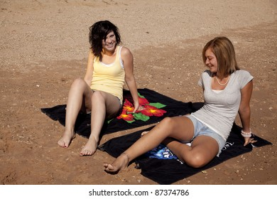 Two women sitting and relaxing on their towles on the beach talking.
