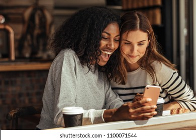 Two women sitting in a restaurant looking at mobile phone and smiling. Friends sitting at a cafe with coffee and snacks on the table looking at a mobile phone.
