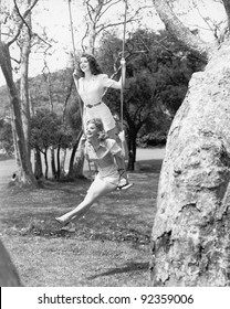 Two women sitting and standing on a swing