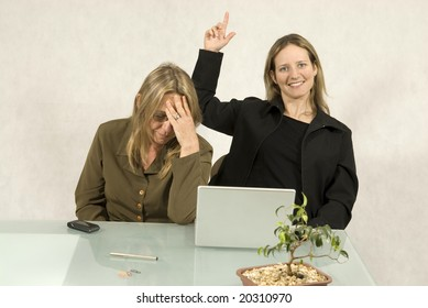 Two Women are sitting at a table in a business meeting.  One woman has her eyes closed and looks stressed.  The other woman is smiling and has her hand pointing upwards.  Horizontally framed shot.