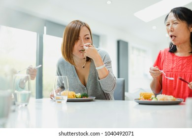 Two women are sitting with their family enjoying a stir fry dinner at home. The mature woman has a mouthful of noodles and the senior woman is laughing.