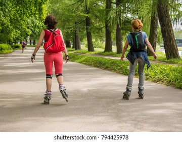 Two women skates on roller in a park. Horizontal back view, outdoor.