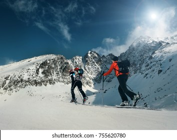 Two women ski walkers go up on the mountain top