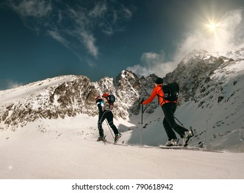 Two women ski walkers go up on the mountain top.