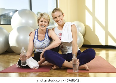 Two women smile towards the camera while sitting on the floor of a gym. One woman has her arm around the other and balance balls can be seen in the background. Horizontal shot.