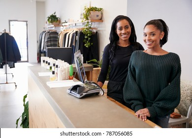 Two women smiling behind the counter in clothing store