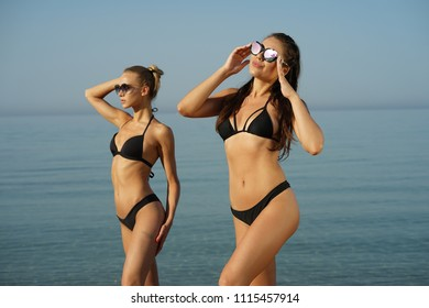 Two women with sporty figure on the beach