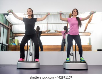 "Two women standing exercise weights, fitness equipment similar to ""Power Plate""."
