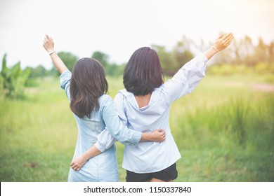 Two women are standing in a field and hugging each other their hands are raised up to the sky in Friendship Day.
