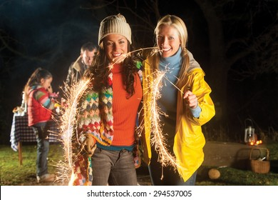 Two women are standing together smiling for the camera with lit sparklers in their hands. They are outside and there are other people in the background behind them.