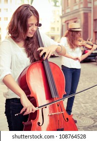 Two women strings duet playing violin and cello on the street of european city. Split toning