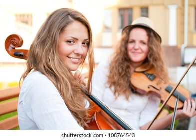 Two women strings duet playing violin and cello on the street of european city