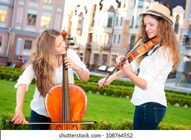Two women strings duet playing violin and cello in city square