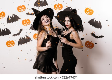 Two women in suits witches posing against a white wall, hung with paper bats, dressed in black witch dresses. Confetti flashes on them and one of them laughs