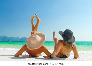 two women sunbathing lying down on the tropical beach summer travel holidays