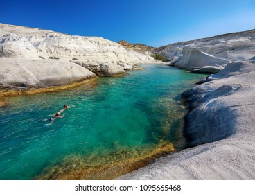 Two women swimming in clear waters of Sarakiniko bay, Milos island, Cyclades, Greece