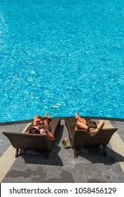 Two Women at the swimming pool at the luxury tropical resort drinking cocktails