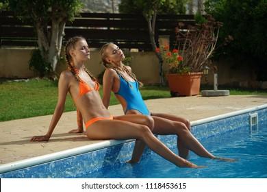 Two women in swimwear sitting by the swimming pool