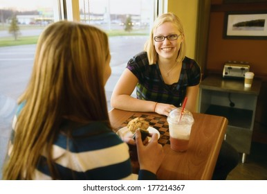 Two Women Talking At A Table In A Cafe
