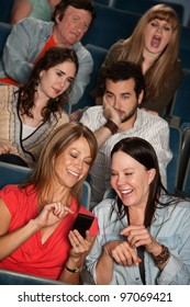 Two women talking in theater with bothered audience