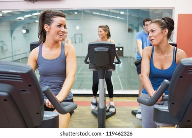 Two women talking while training in a spinning class in gym