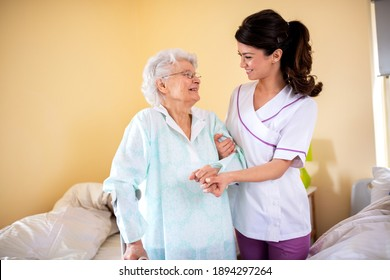 Two women teamwork, lady doctor holding senior woman resident by her arm helping her to walk