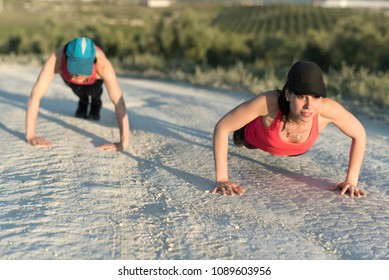 Two women training push ups in the road