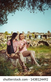 Two women travelers searching right direction on map, freedom and active lifestyle concept