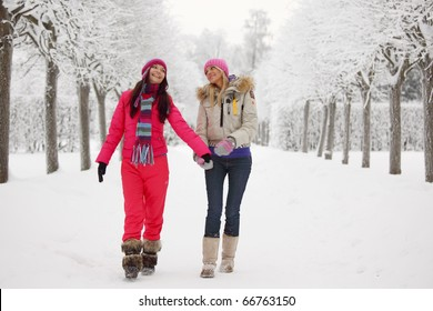 two women walk by winter alley