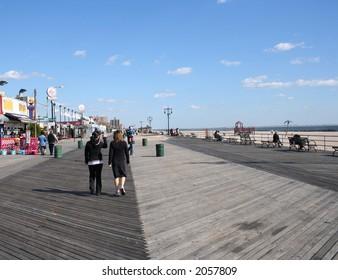 Two women walking along Coney Island boardwalk Brooklyn New York