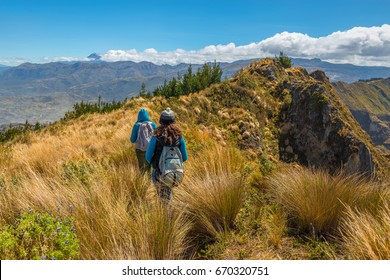Two women walking along the famous Quilotoa Loop trekking in the Andes mountain range of Ecuador near Quito, South America.