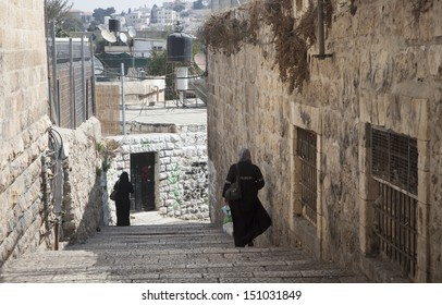 Two women walking away on an old Jerusalem street with modern satellite dishes in the background