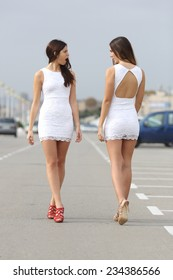 Two women walking on the street with the same dress looking each other with hate