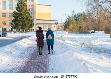 Two women are walking in the park on a winter day. One woman on crutches