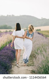Two women walking together at lavender field