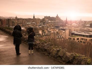 Two women watching the city of Edinburgh at sunset.